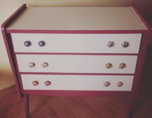 Commode des années 50 relookkée en violet et gris avec de grands boutons de porte colorés